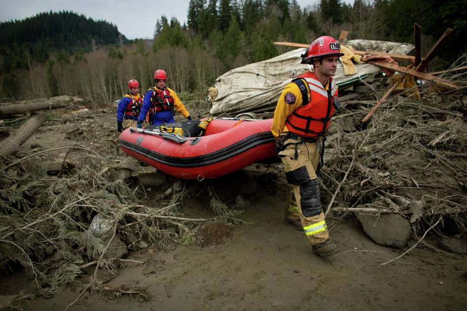 Rescue workers carry a boat into the mudslide debris near Oso, Wash. In the wake of Saturday's mudslide in Snohomish County, there have been  over 150 reports of missing people or unaccounted individuals and dozens  of bodies found in the debris. Photo: JOSHUA TRUJILLO, SEATTLEPI.COM / SEATTLEPI.COM