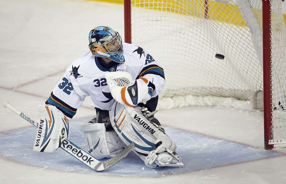 San Jose Sharks goalie Alex Stalock looks back as the winning shootout goal enters the net during overtime NHL hockey action against the Calgary Flames in Calgary, Monday, March 24, 2014. The Flames beat the Sharks 2-1 in a shootout. (AP Photo/The Canadian Press, Jeff McIntosh) Photo: Jeff McIntosh, Associated Press