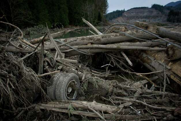 The rear wheels of a truck are shown in the mudslide debris. Photo: JOSHUA TRUJILLO, SEATTLEPI.COM / SEATTLEPI.COM