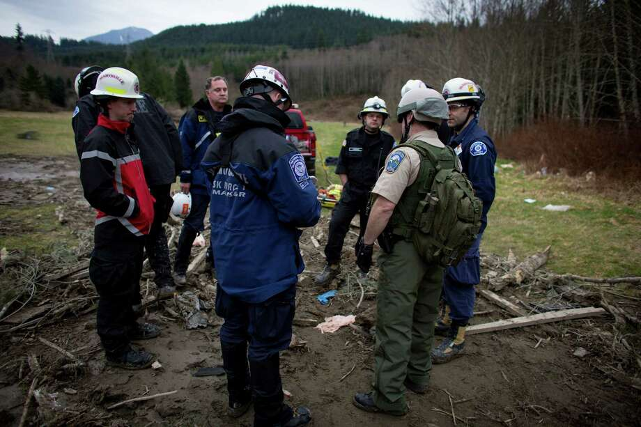 Rescue workers and members of the FEMA National Response Team gather at the edge of a mudslide near Oso, Wash. Federal Government assets arrived at the scene on Tuesday. Photo: JOSHUA TRUJILLO, SEATTLEPI.COM / SEATTLEPI.COM