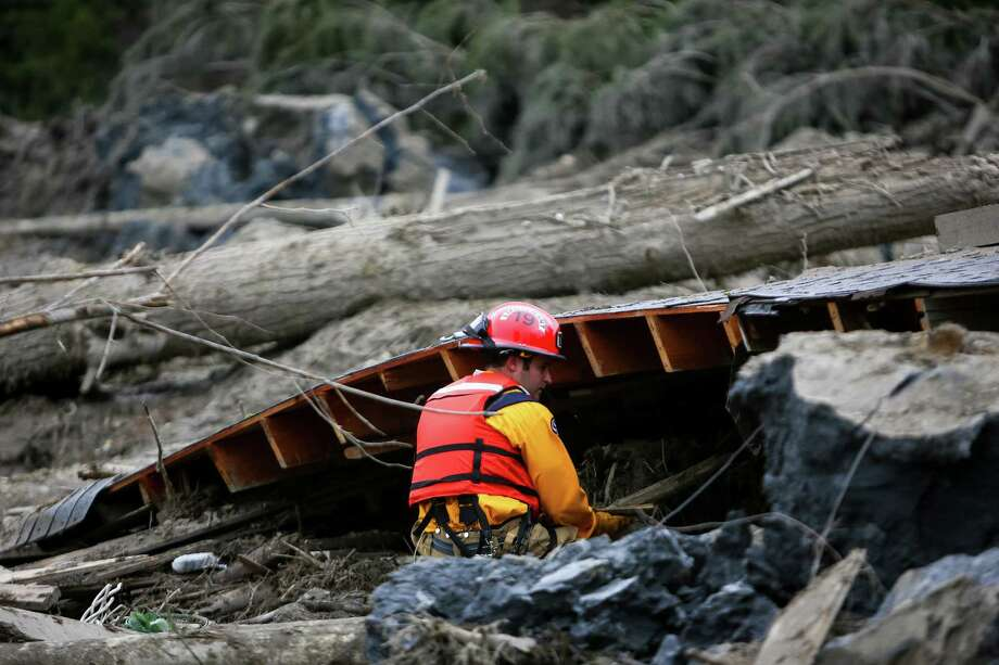 A rescue worker looks under the roof of a destroyed home near Oso, Wash. Photo: JOSHUA TRUJILLO, SEATTLEPI.COM / SEATTLEPI.COM