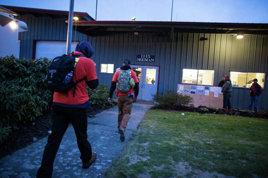 Local, volunteer rescue workers arrive at the Darrington, Wash. Fire Department after a call was put out for help from