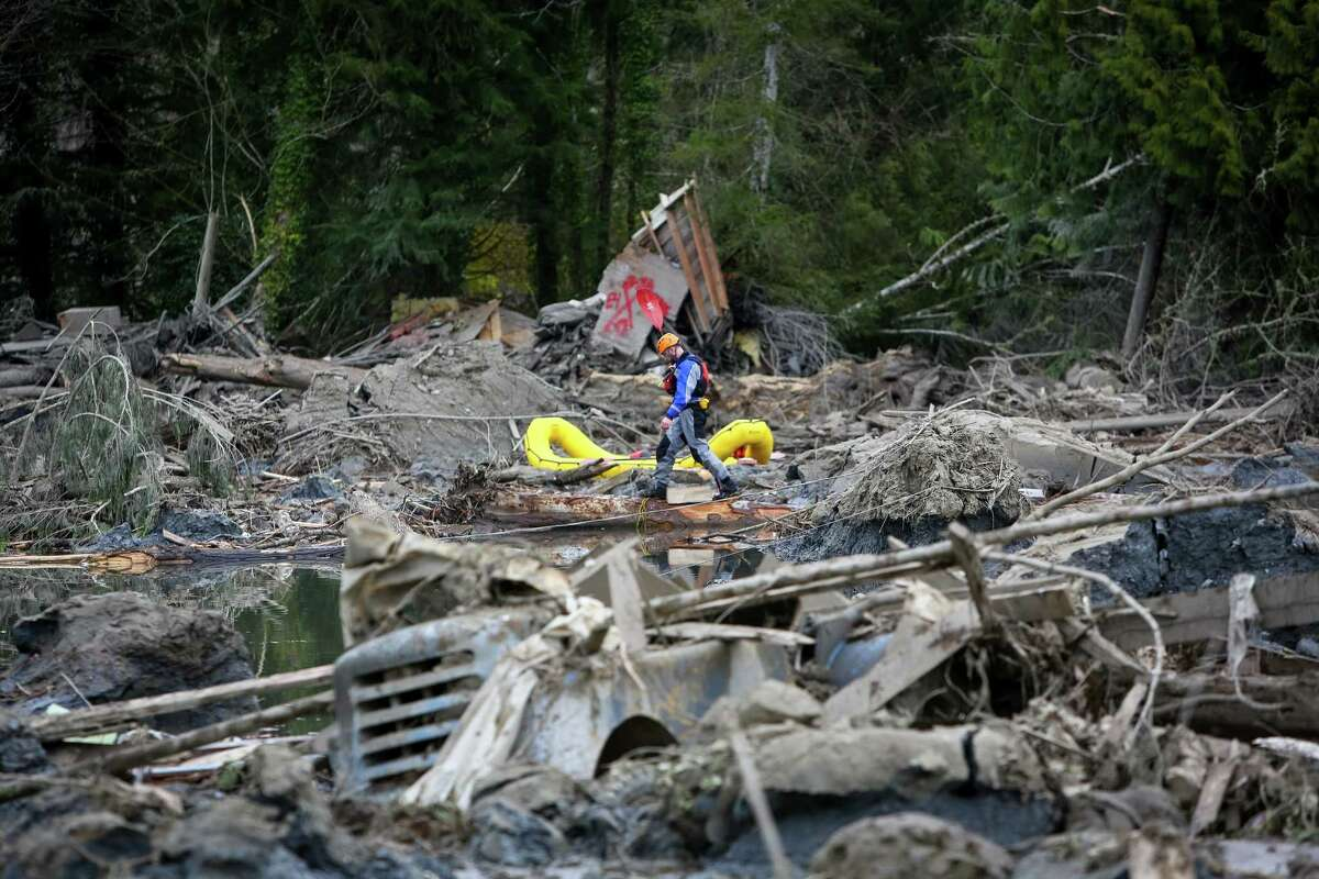 A rescue worker negotiates the debris field near Oso, Wash.