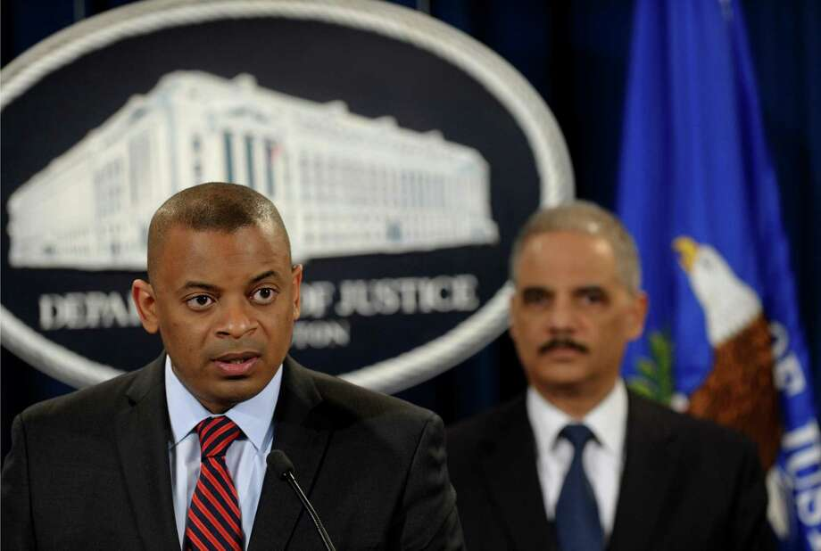 Transportation Secretary Anthony Foxx. left, accompanied by Attorney General Eric Holder, talks about a $1.2 billion settlement with Toyota over its disclosure of safety problems, Wednesday, March 19, 2014, during a news conference at the Justice Department in Washington.  (AP Photo/Susan Walsh) ORG XMIT: DCSW107 Photo: Susan Walsh / AP