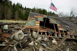 Damage is shown near Oso, Wash. In the wake of Saturday's mudslide on Highway 530 in Snohomish County, there have been 176 reports of missing people or unaccounted individuals and the death toll has risen to 14. The flag flown in the debris was hoisted by neighbors after it was found unsoiled in the mess. Photographed on Tuesday, March 25, 2014.