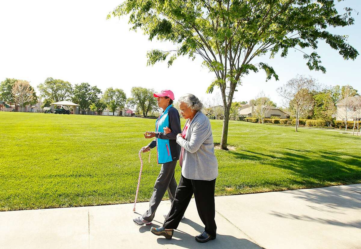 Denise Elarms, left, a retired firefighter who has cancer, walks in her Elk Grove neighborhood with her mother, Catherine.