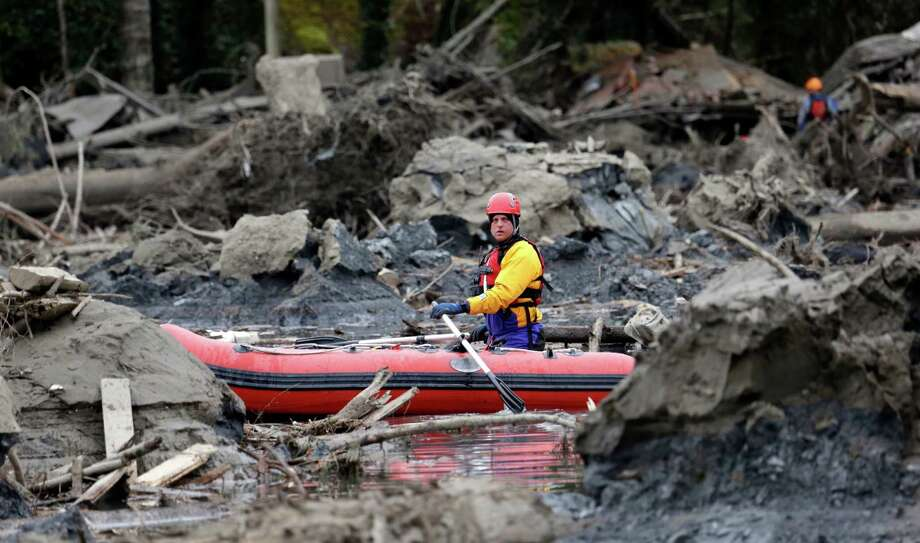A searcher uses a small boat to look through debris from a deadly mudslide Tuesday in Oso, Wash. At least 14 people died in the square-mile slide that hit in the rural area 55 miles northeast of Seattle on Saturday. Photo: Elaine Thompson, STF / AP