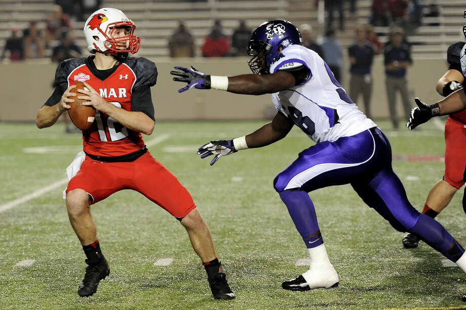 Lamar Cardinal's Caleb Berry, 12, looks for a receiver while under pressure from a Stephen F. Austin player during a game last season. Lamar unveiled its schedule for the 2014 season on Tuesday. Enterprise file photo Photo: Drew Loker / ©2013. www.drewloker.com