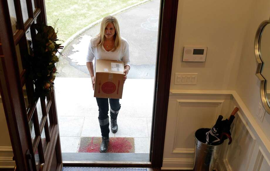 Mimi Shalhoub carries in her ready-to-cook dinner kits from Plated.com Tuesday, Mar. 25, 2014, at her home in Fairfield, Conn. The box, delivered right to her door, contains everything needed to prepare a gourmet meal. Photo: Autumn Driscoll / Connecticut Post