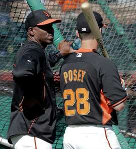 San Francisco Giants former player Barry Bonds, left, chats with catcher Buster Posey during batting practice before a spring training baseball game between the Giants and the Chicago Cubs in Scottsdale, Ariz., Monday, March 10, 2014. Bonds starts a seven day coaching stint today. (AP Photo/Chris Carlson)