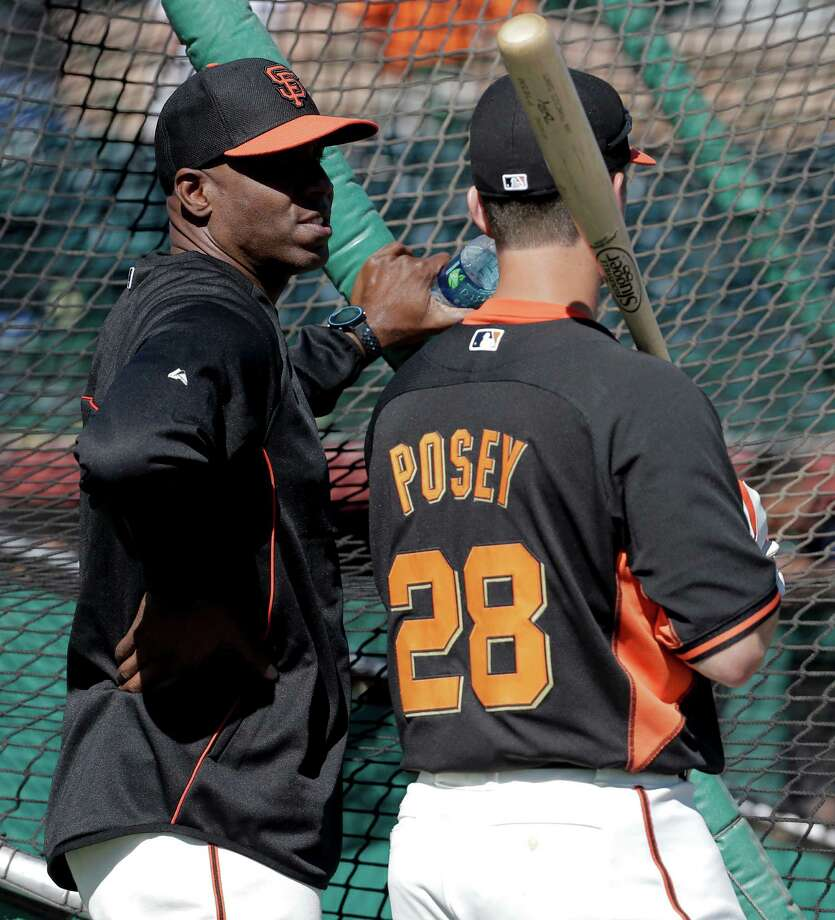 San Francisco Giants former player Barry Bonds, left, chats with catcher Buster Posey during batting practice before a spring training baseball game between the Giants and the Chicago Cubs in Scottsdale, Ariz., Monday, March 10, 2014. Bonds starts a seven day coaching stint today. (AP Photo/Chris Carlson) Photo: Chris Carlson / Associated Press / AP