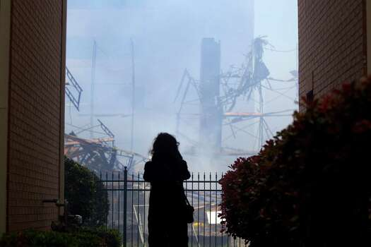 A woman watches as firefighters battled a large 5-alarm blaze Tuesday afternoon at an apartment building under construction on West Dallas near Montrose Tuesday, March 25, 2014, in Houston. Flames engulfed the apartment complex as 200 firefighters in 80 units fought to gain an upper hand on the blaze. The five-story, 368-unit building was destroyed. No injuries were reported. Photo: Johnny Hanson, Houston Chronicle / © 2014  Houston Chronicle