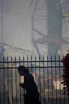 A woman walks past as firefighters battled a large 5-alarm blaze Tuesday afternoon at an apartment building under construction on West Dallas near Montrose Tuesday, March 25, 2014, in Houston. Flames engulfed the apartment complex as 200 firefighters in 80 units fought to gain an upper hand on the blaze. The five-story, 368-unit building was destroyed. No injuries were reported. Photo: Johnny Hanson, Houston Chronicle / © 2014  Houston Chronicle