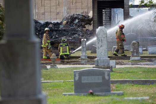 From the Magnolia Cemetery of Houston firefighters battled a large 5-alarm blaze Tuesday afternoon at an apartment building under construction on West Dallas near Montrose Tuesday, March 25, 2014, in Houston. Flames engulfed the apartment complex as 200 firefighters in 80 units fought to gain an upper hand on the blaze. The five-story, 368-unit building was destroyed. No injuries were reported. Photo: Johnny Hanson, Houston Chronicle / © 2014  Houston Chronicle
