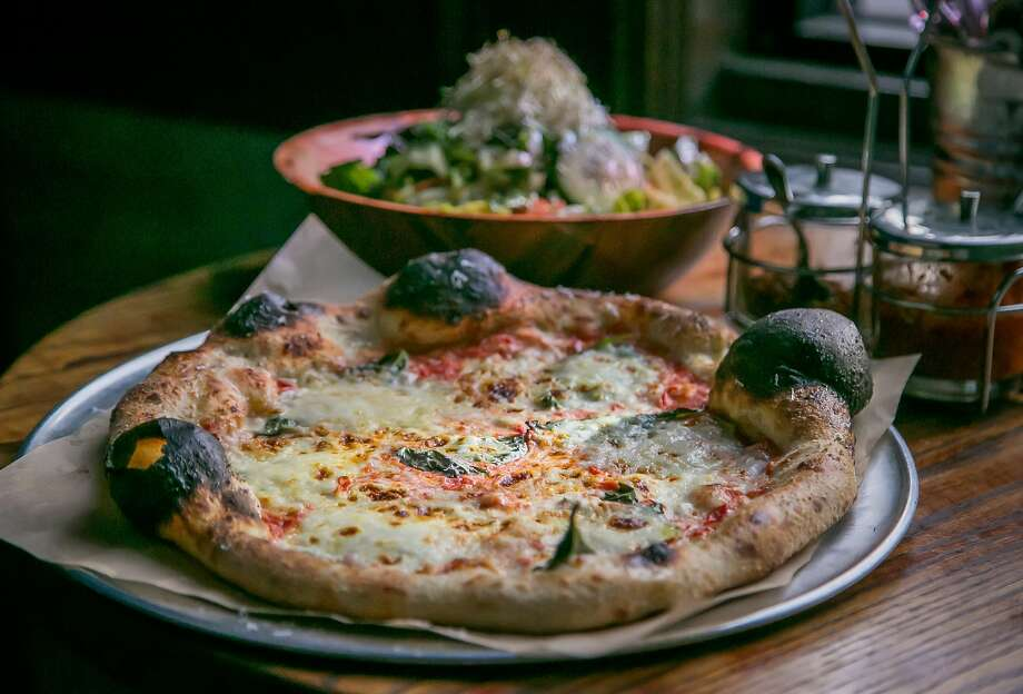 Most groups of diners at the popular Pizzahacker restaurant in Bernal Heights order a huge Intermezzo salad to accompany their Neapolitan-style pizza, such as this margherita. Photo: John Storey, Special To The Chronicle