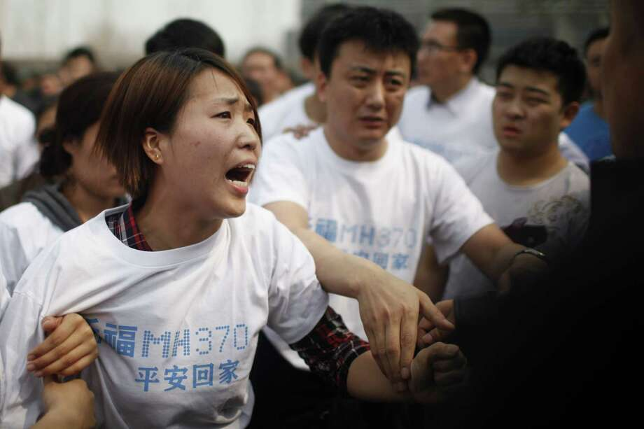 A relative of passengers on missing Malaysia Airlines flight MH370 yells at a security personnel outside the Malaysian embassy in Beijing. Photo: AFP, Stringer / AFP