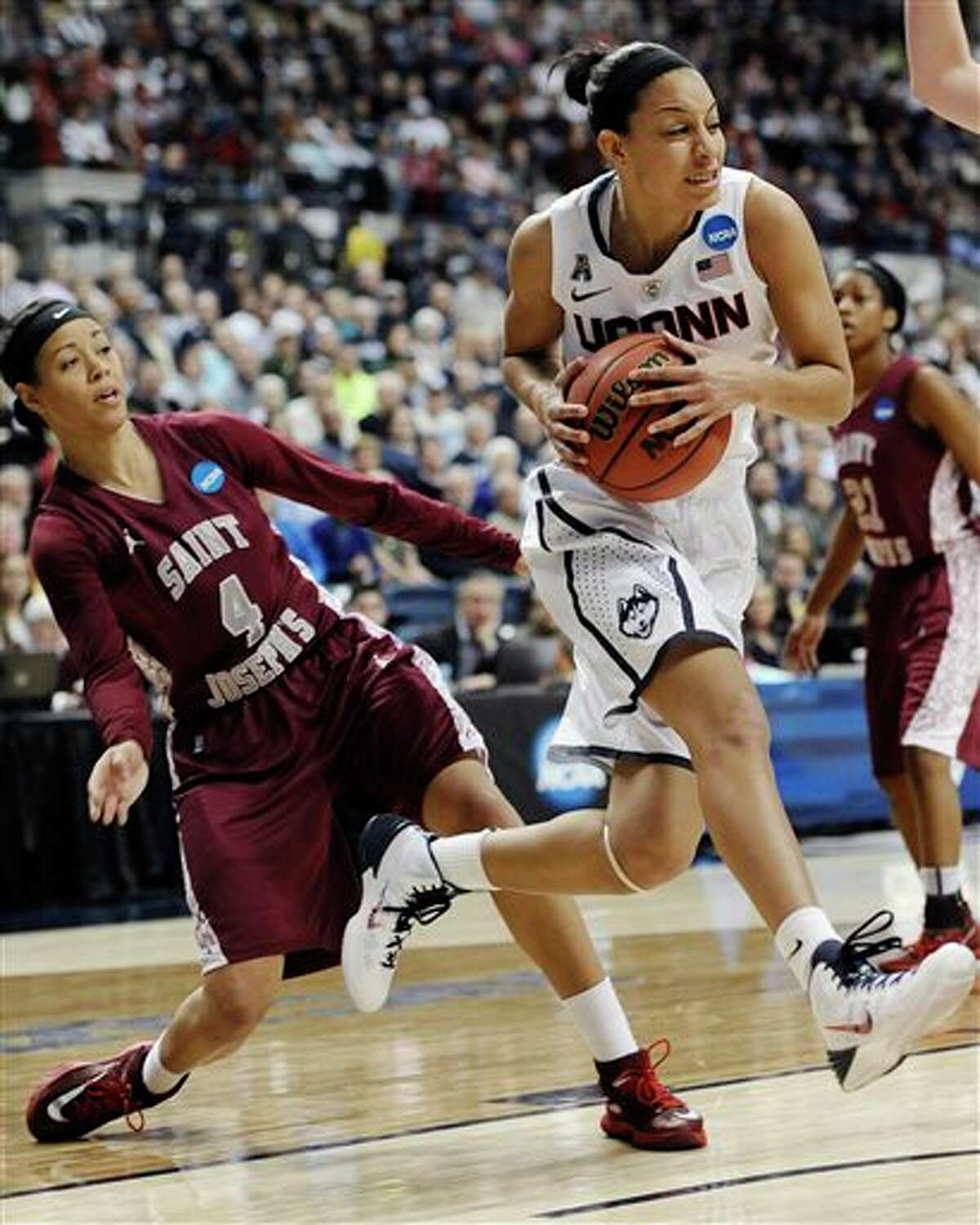 Connecticut's Bria Hartley, right, drives past Saint Joseph's Natasha Cloud, left, during the first half of a second-round game of the NCAA women's college basketball tournament, Tuesday, March 25, 2014, in Storrs, Conn. (AP Photo/Jessica Hill)