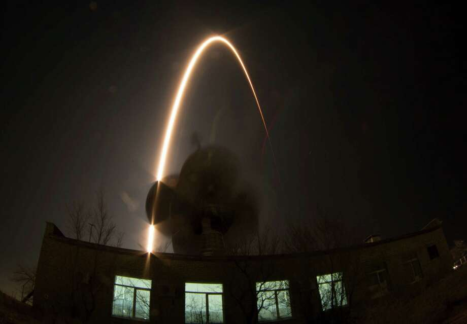In this photo taken with a fisheye lens and long exposure, the Soyuz-FG rocket booster with Soyuz TMA-12M space ship carrying a new crew to the International Space Station (ISS) blasts off over an antenna at the Russian leased Baikonur cosmodrome, Kazakhstan, Wednesday, March 26, 2014. The Russian rocket carries U.S. astronaut Steven Swanson, Russian cosmonauts Alexander Skvortsov and Oleg Artemyev. (AP Photo/Dmitry Lovetsky) Photo: Dmitry Lovetsky, STF / AP