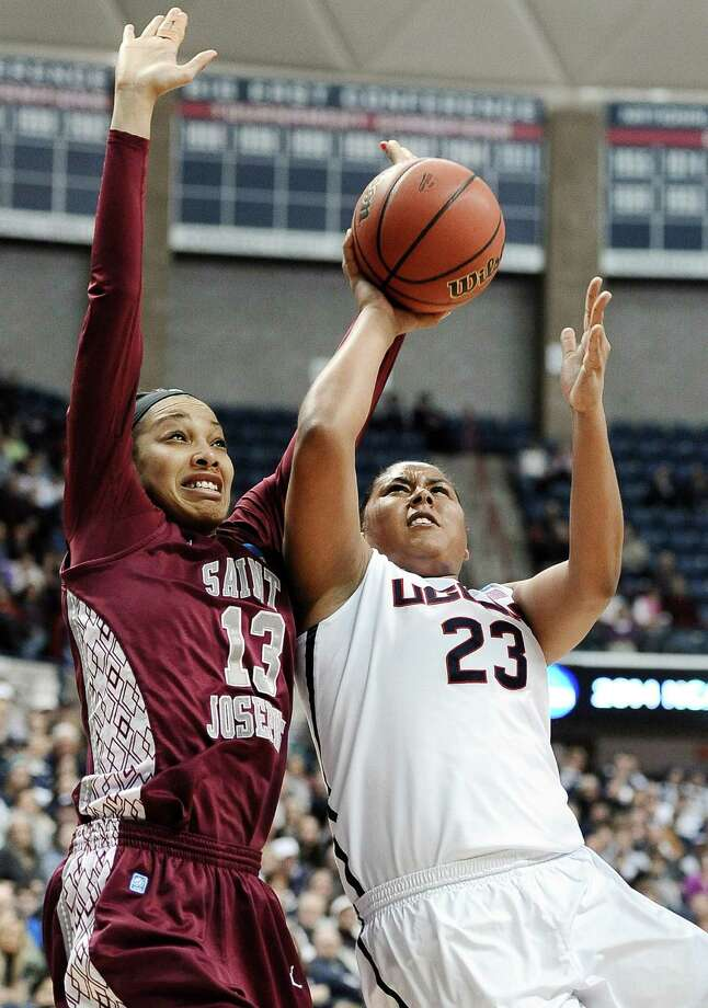 Saint Joseph's Ashley Robinson, left, fouls Connecticut's Kaleena Mosqueda-Lewis, right, as she makes a basket during the first half of a second-round game of the NCAA women's college basketball tournament, Tuesday, March 25, 2014, in Storrs, Conn. (AP Photo/Jessica Hill) Photo: Jessica Hill, Associated Press / Associated Press