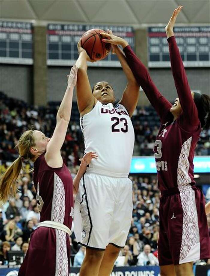 Connecticut's Kaleena  Mosqueda-Lewis goes up for a basket as Saint Joseph's Erin Shields,  left, and Ashley Robinson, right, defend during the first half of a  second-round game of the NCAA women's college basketball tournament,  Tuesday, March 25, 2014, in Storrs, Conn. (AP Photo/Jessica Hill)