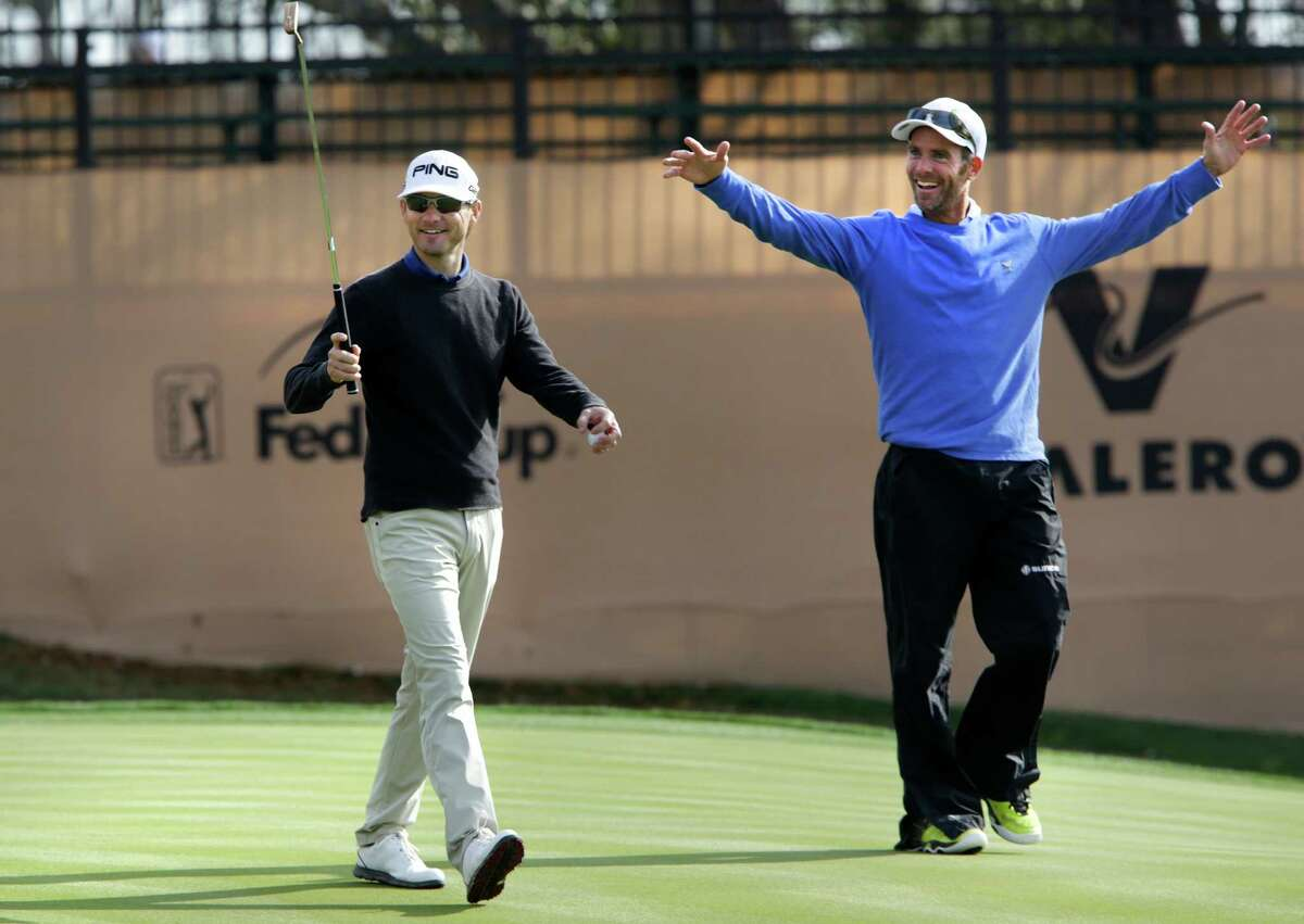 Heath Slocum, left, and his caddie wave to fans as they walk off the 18th green after a practice round preparing for the 2014 Valero Texas Open on the TPC San Antonio AT&T Oaks Course. Tuesday, March 25, 2014.