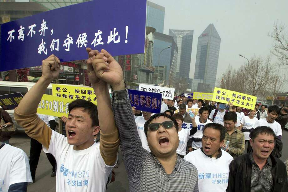 Angry Chinese relatives of passengers onboard the missing Malaysia Airlines plane shout in protest and march toward the Malaysian Embassy in Beijing. Photo: Ng Han Guan / Associated Press / AP