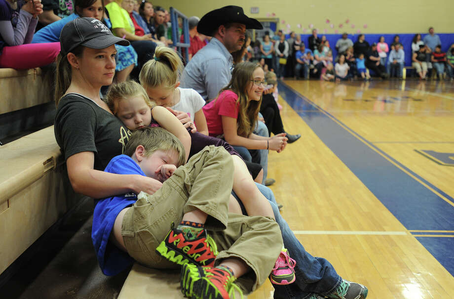 The Hamshire-Fannett gymnasium was filled with curious residents Tuesday night during a special meeting to address the condition and future of the area's elementary school that recently burned. Amanda Cox holds Audrey Cox, 7 and Riley Cox, 4 during the meeting. Photo taken Tuesday, March 25, 2014 Guiseppe Barranco/@spotnewsshooter Photo: Guiseppe Barranco, Photo Editor