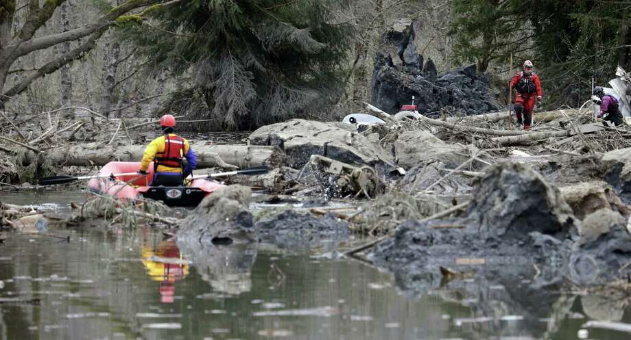 Searchers in Oso, Wash., look through the debris left by the deadly mudslide. Scores of people are still unaccounted for in the wake of Saturday's catastrophe. Photo: Elaine Thompson / Associated Press / AP