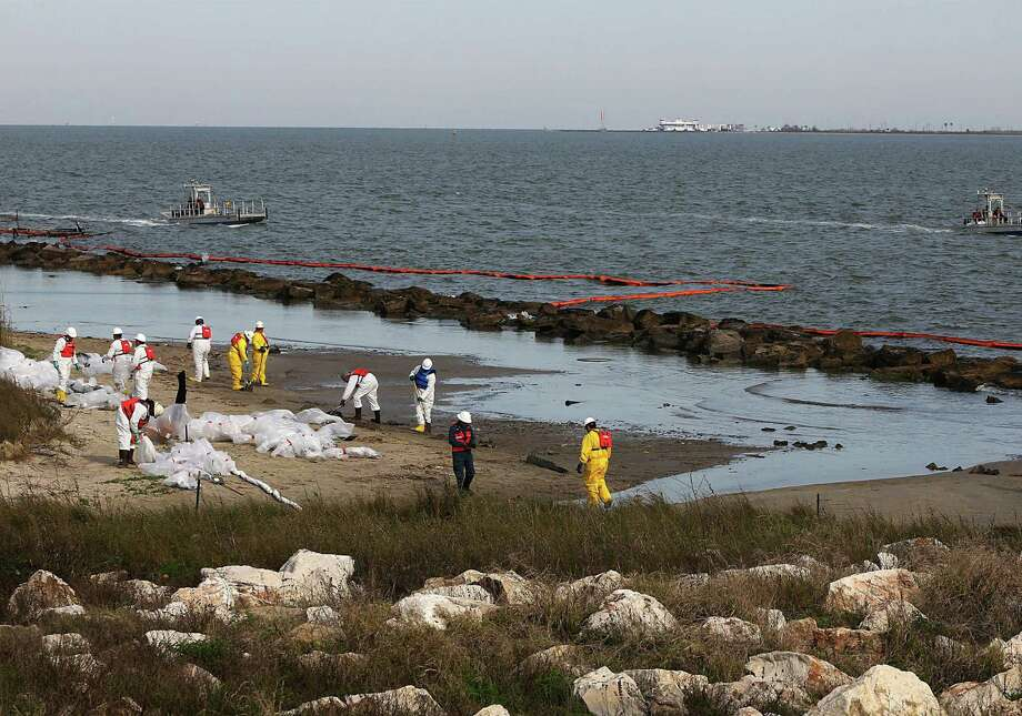 Garner Environmental Services crews clean up oil at East Beach on the Houston Ship Channel. Saturday's collision spilled as much as 168,000 gallons of oil into Galveston Bay. Photo: Thomas Shea / Getty Images / 2014 Getty Images