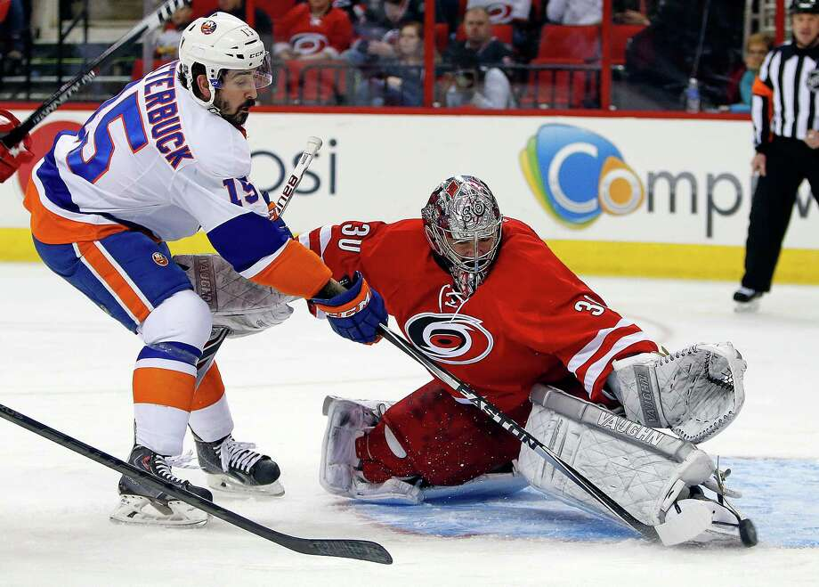 New York Islanders' Cal Clutterbuck (15) pokes the puck past Carolina Hurricanes goalie Cam Ward (30) for a goal during the first period of an NHL hockey game in Raleigh, N.C., Tuesday, March 25, 2014. (AP Photo/Karl B DeBlaker) ORG XMIT: NCKD101 Photo: Karl B DeBlaker / FR7226 AP