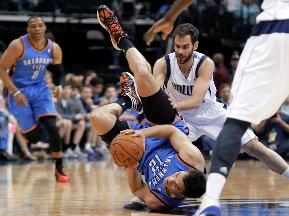 Oklahoma City Thunder center Steven Adams (12) goes down with the ball against Dallas Mavericks guard Jose Calderon, of Span, during the first half of an NBA basketball game Tuesday, March 25, 2014, in Dallas. (AP Photo/LM Otero) ORG XMIT: DNA102 Photo: LM Otero / AP