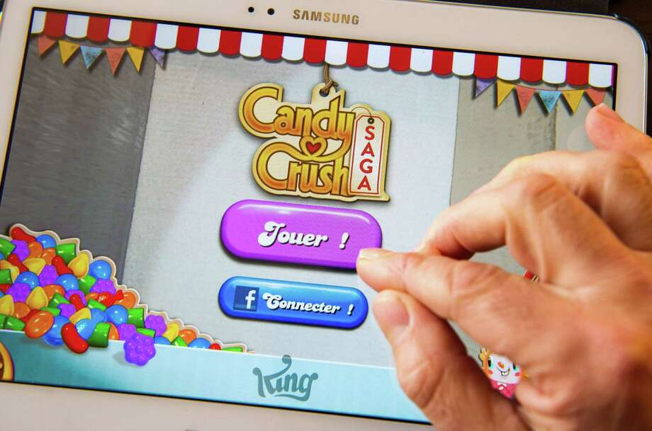 "King Digital Entertainment, the creator of the wildly popular video game ""Candy Crush,"" priced its initial public offering at $22.50 per share, raising $500 million. Photo: PHILIPPE HUGUEN, Staff / AFP ImageForum"