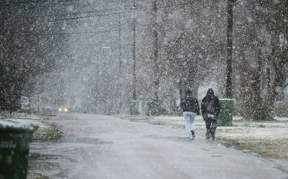 Stephenie Wilkins, left, and Sevon Twyford walk down the street in a heavy snowfall after leaving work for the day at New Ravenna in Exmore, Va. on Tuesday, March 25, 2014. (AP Photo/Jay Diem, Eastern Shore News) NO SALES Photo: Jay Diem, Associated Press