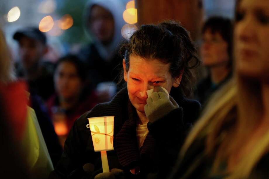 Teresa Welter cries as she holds a candle during a candlelight vigil in Arlington for the victims of the massive mudslide. Photo: Ted S. Warren, AP / AP