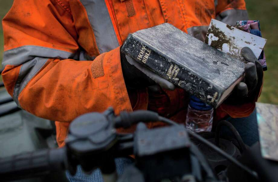 Elaine Young holds a Bible she pulled from the mudslide debris near Oso, Wash.  Photo: JOSHUA TRUJILLO, SEATTLEPI.COM / SEATTLEPI.COM