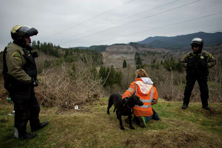 Elaine Young looks down on her flooded property and house with her dog Bo as she talks with Snohomish County Sheriff's deputies near Oso, Wash. Young's home was spared by the mudslide but the dam it created caused the Stillaguamish river to flood part of her home. Photo: JOSHUA TRUJILLO, SEATTLEPI.COM / SEATTLEPI.COM