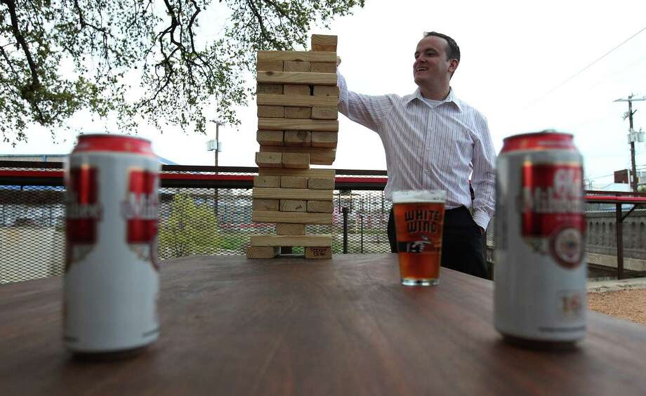 Patron Alfredo Arias plays with a giant wooden block puzzle at the new TacoLand. Photo: Kin Man Hui, San Antonio Express-News / ©2013 San Antonio Express-News