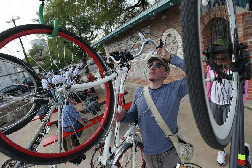 Patron Nicholas Kenna hangs a friend's bike at the entrance of the new TacoLand.