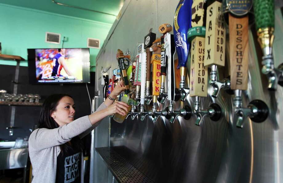 Bartender Mayra Arias pours a beer from the new draft wall at TacoLand. Photo: Kin Man Hui, San Antonio Express-News / ©2013 San Antonio Express-News