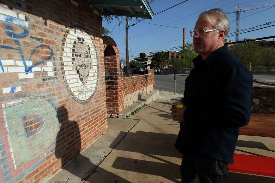 "TacoLand owner Chris Erck talks about some aspects of the newly bar that still honors Ramiro ""Ram"" Ayala, the original owner of Taco Land, such as the mural of Ayala by the front of the business. Photo: Kin Man Hui, San Antonio Express-News / ©2013 San Antonio Express-News"