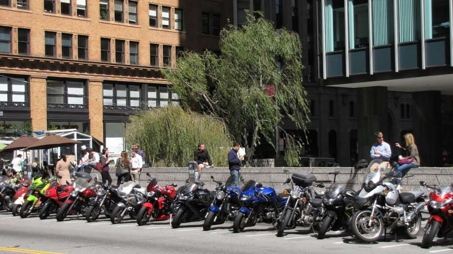 A good public space can be nothing more than a broad ledge with midday sun. The Sansome Street edge of 1 Bush St. routinely gets more patronage than the handsome but overly artful sunken plaza on the other side of the ledge. You've got trees, motorcycles, tall buildings of multiple styles and all those FiDi people to watch -- what's not to like? Photo: John King, The Chronicle
