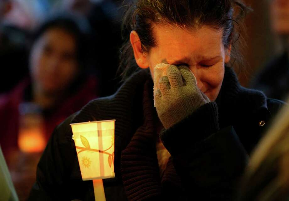 Teresa Welter cries as she holds a candle on Tuesday at a candlelight vigil in Arlington for the victims of a massive mudslide that struck the nearby community of Oso on Saturday. Photo: Ted S. Warren, Associated Press / AP2014
