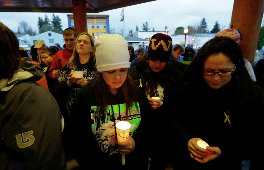 People gather Tuesday at a candlelight vigil in Arlington for the victims of a massive mudslide that struck the nearby community of Oso on Saturday. Photo: Ted S. Warren, Associated Press / AP2014