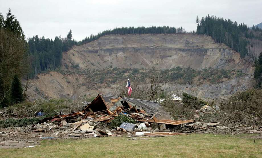 A flag, put up by volunteers helping search the area, stands on Tuesday in the ruins of a home left at the end of a deadly mudslide from the now-barren hillside seen about a mile behind.  Photo: Elaine Thompson, Associated Press / AP2014