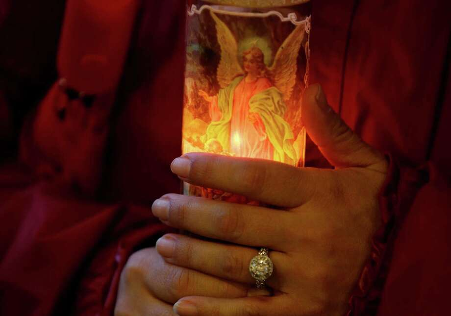 Anna Schoneker holds a guardian angel candle Tuesday at a candlelight vigil in Arlington for the victims of a massive mudslide that struck the nearby community of Oso on Saturday. Photo: Ted S. Warren, Associated Press / AP2014