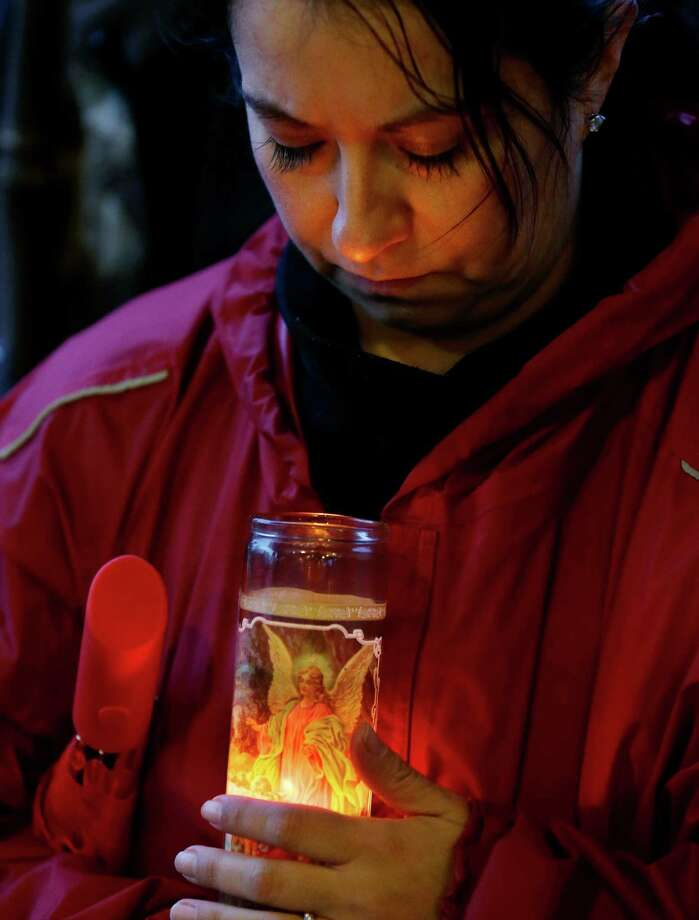 Anna Schoneker holds a guardian angel candle Tuesday, March 25, 2014, at a candlelight vigil in Arlington, Wash., for the victims of a massive mudslide that struck the nearby community of Oso, Wash., on Saturday, killing at least 16 people and leaving dozens missing. (AP Photo/Ted S. Warren) Photo: Ted S. Warren, Associated Press / AP2014