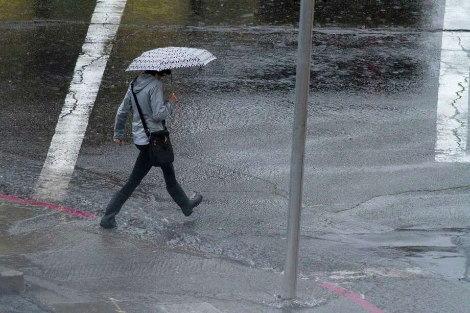 A pedestrian walks over a stream of water on a  curbside in Oakland during a downpour Wednesday morning March 26, 2014. Photo: SF Gate / Douglas Zimmerman