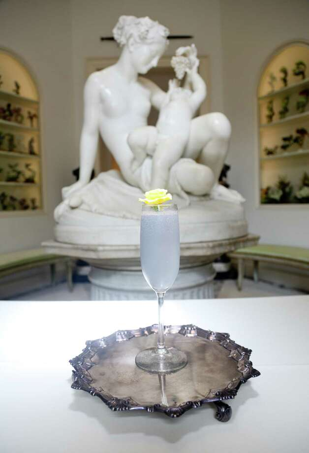 "3/3/14: Queen Bee. 1 1/2 oz dry gin, 1/2 oz of Creme-de-violette. 1/2 oz of lemon juice, 1/2 oz of simple syrup 1:1 shake pour in a flute glass ; top with dry Champagne and add flower.   The photograph was taken with the entrance way statue Giovanni Maria Benzoni, Young Dionysus with a Nymph, 1866, marble at the the Museum of Fine Arts, Houston, The Rienzi Collection, in Houston, Texas. It was a gift by Mr. and Mrs. Harris Masterson III.  Rienzi, the Museum of Fine Arts Houston's museum for European decorative arts, will be the site of a special dinner on April 16 called ""Gin Craze."" The evening's meal courses and cocktails will celebrate the history of gin. It will be prepared by Richard Knight, Benjy Mason (who are partnering in the upcoming Hunky Dory restaurant), Photo: Thomas B. Shea / © 2014 Thomas B. Shea"
