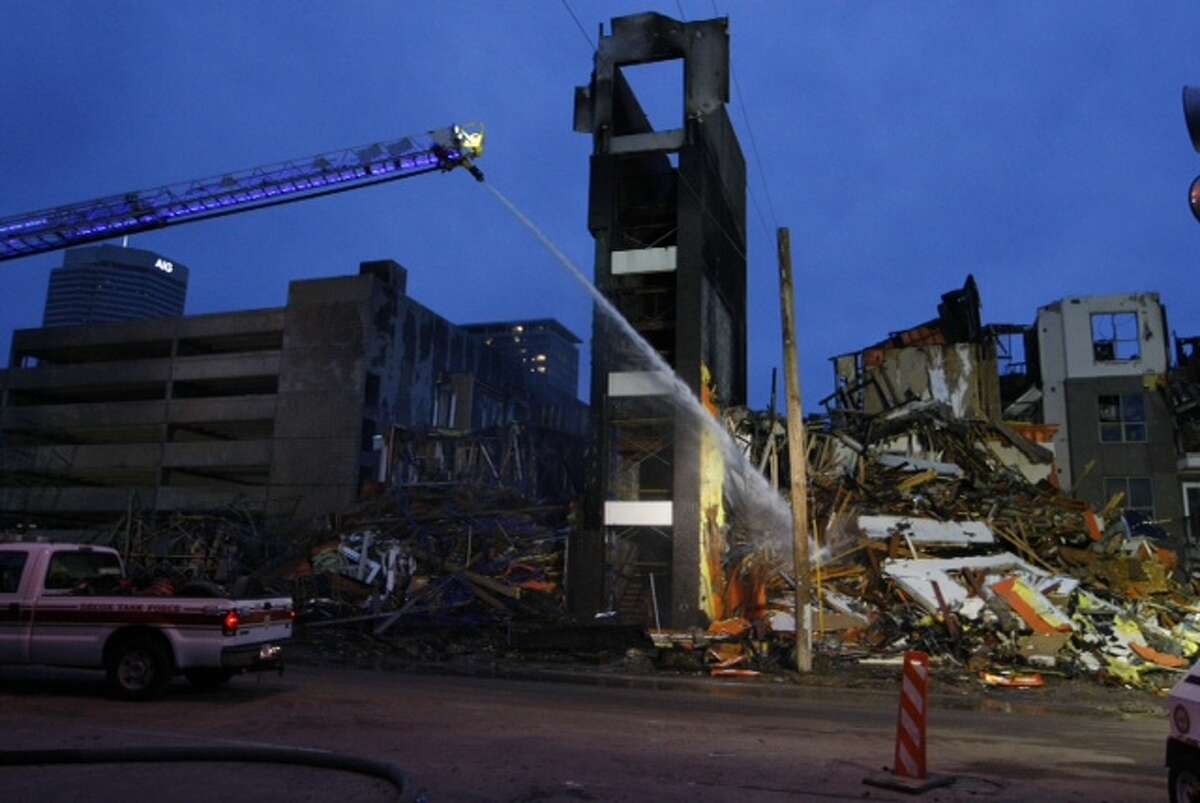 Houston firefighters continued to douse hot spots Wednesday morning, the day after a five-alarm inferno consumed an apartment complex under construction near downtown.