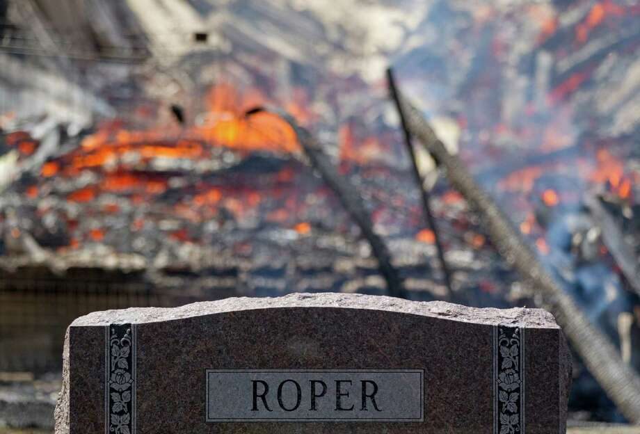 A gravestone in the Magnolia Cemetery of Houston where firefighters battled a large 5-alarm blaze Tuesday afternoon at an apartment building under construction on West Dallas near Montrose Tuesday, March 25, 2014, in Houston. Flames engulfed the apartment complex as 200 firefighters in 80 units fought to gain an upper hand on the blaze. The five-story, 368-unit building was destroyed. No injuries were reported. Photo: Johnny Hanson, Houston Chronicle / © 2014  Houston Chronicle